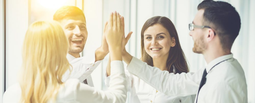The four business people greeting with a high five on the sun background